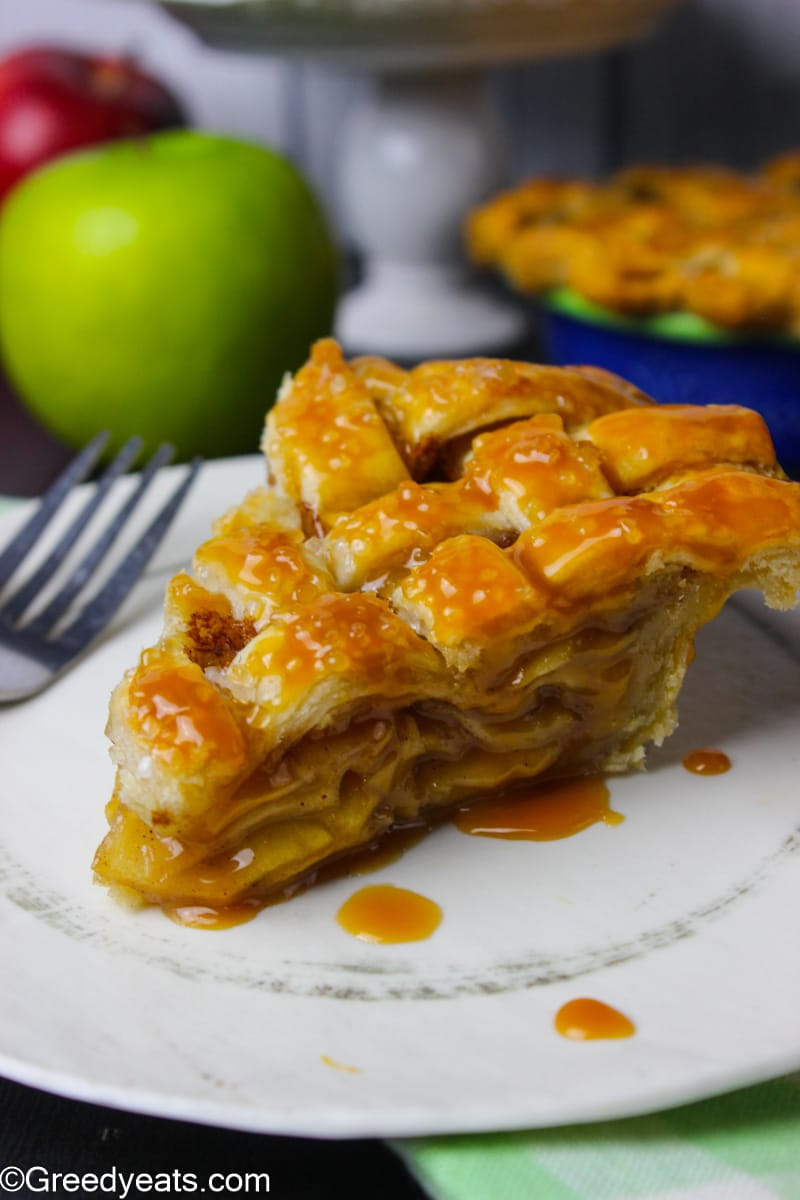 A slice of Apple Pie baked with lattice pie crust and homemade apple pie filling.