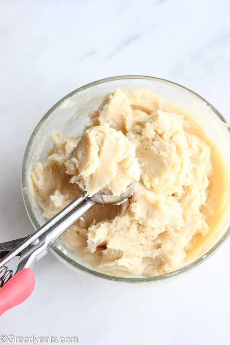Chilled cream cheese cookie dough in a glass bowl with a cookie scoop in it.