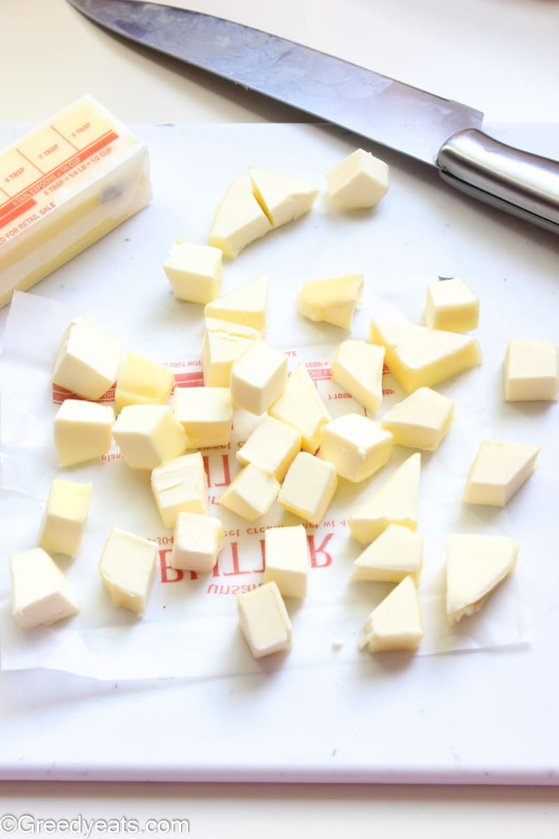 Cold butter cubes on a white board for pie dough