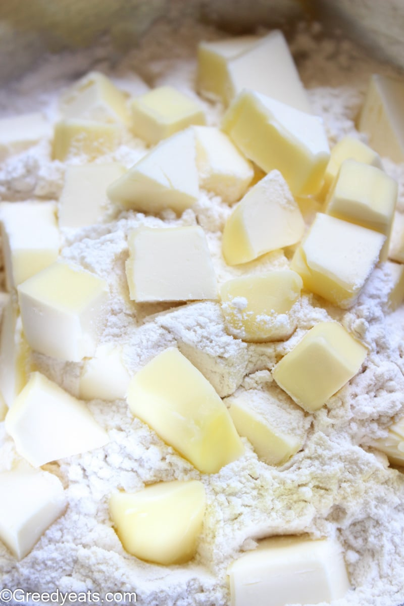 Butter cubes in flour to be cut into pea sized crumbs.