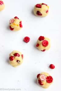Chilled cranberry cookie dough balls ready to be baked.