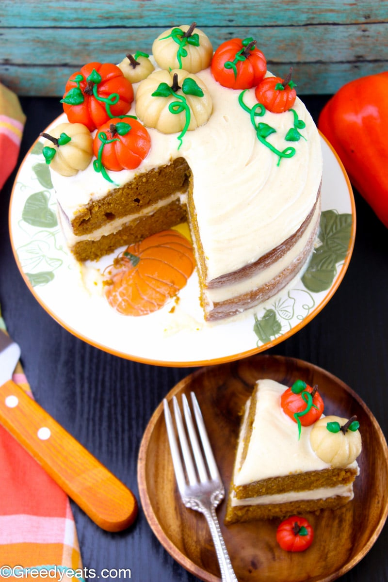 Homemade pumpkin cake on a fall themed orange cake stand with a slice of cake on a wooden plate..