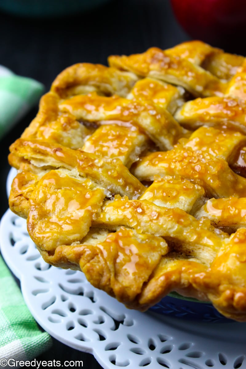 Mini apple pie with lattice crust on top that has baked super flaky.