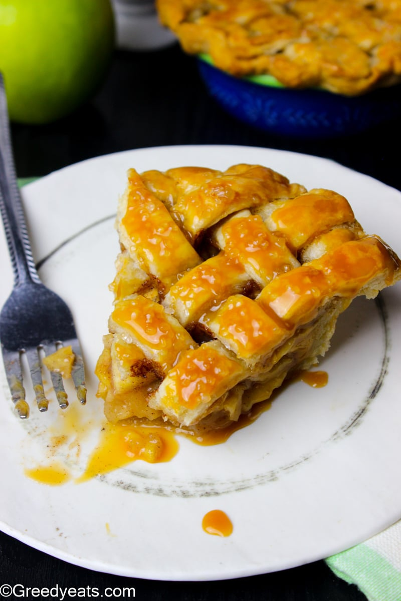 A slice of Apple Pie baked with lattice pie design,drizzled with caramel.