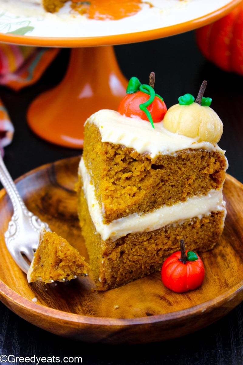 Moist Pumpkin Cake topped with fondant pumpkins and frosted with cream cheese frosting.