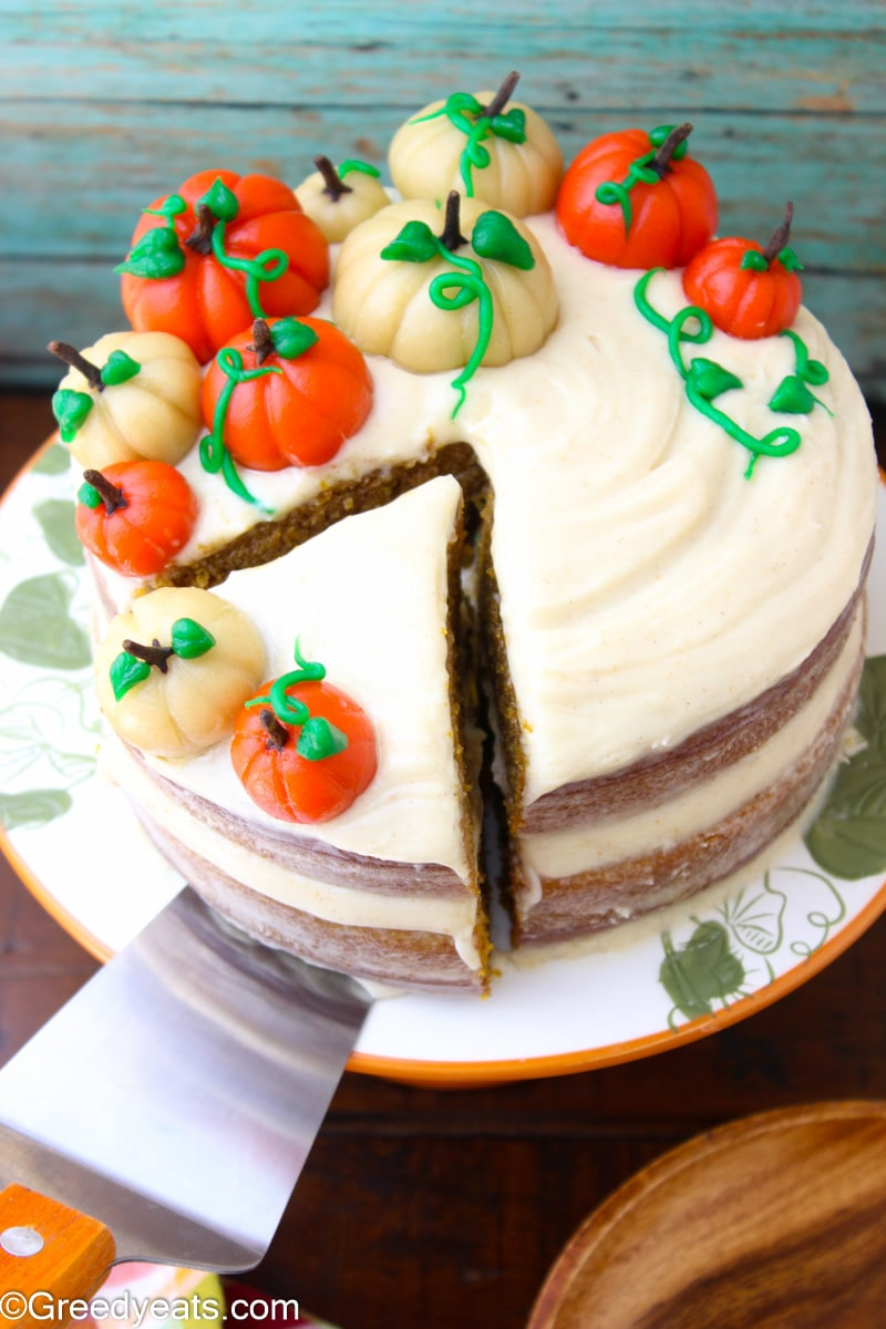 9 inches layered Pumpkin Cake topped with cream cheese frosting on a fall themed cake stand.