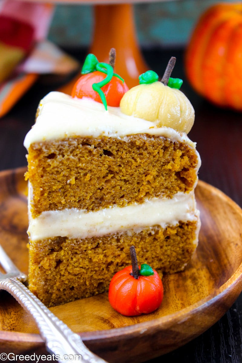 A slice of Layered Pumpkin Cake smothered in sweet and tangy cream cheese frosting!