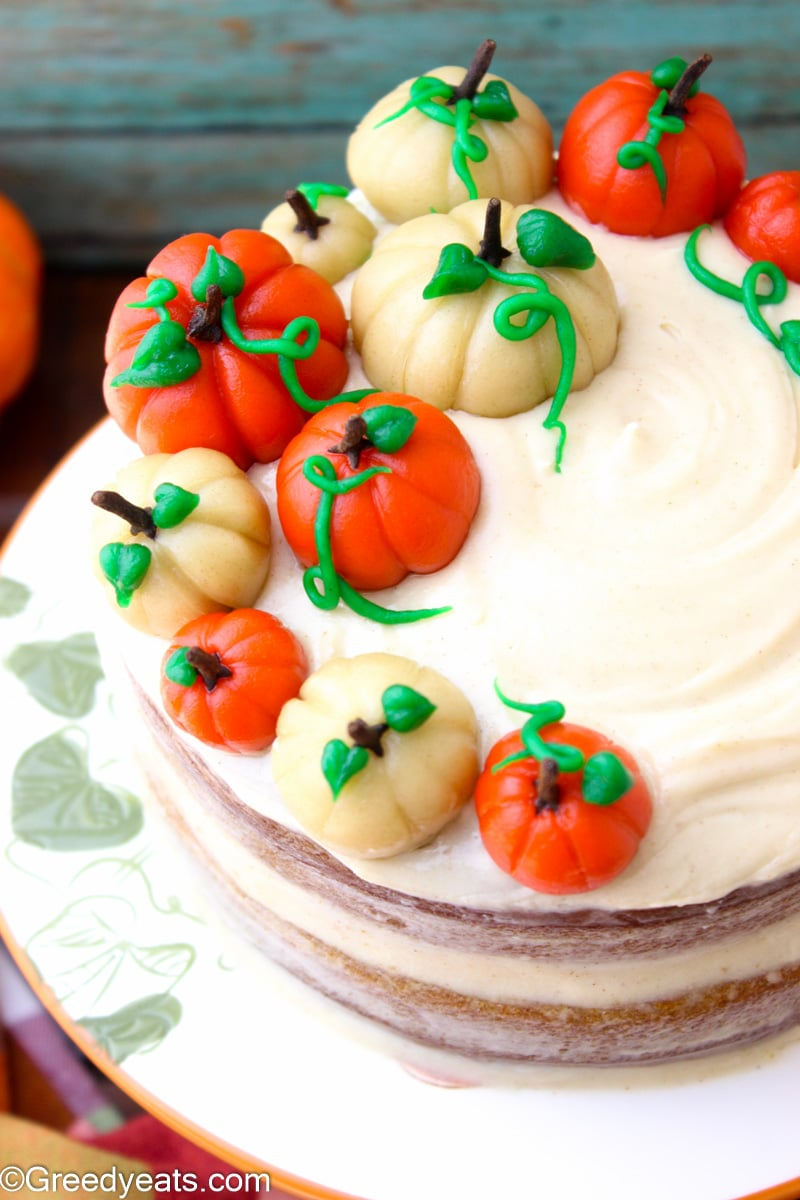Easy Pumpkin Spice Cake frosted with cream cheese frosting and fondant pumpkin toppers.