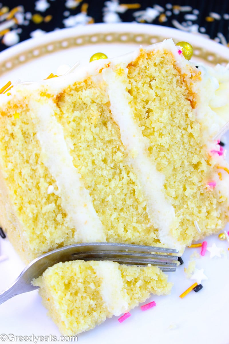 A slice of homemade Vanilla Cake with creamy layers of Vanilla Buttercream frosting!