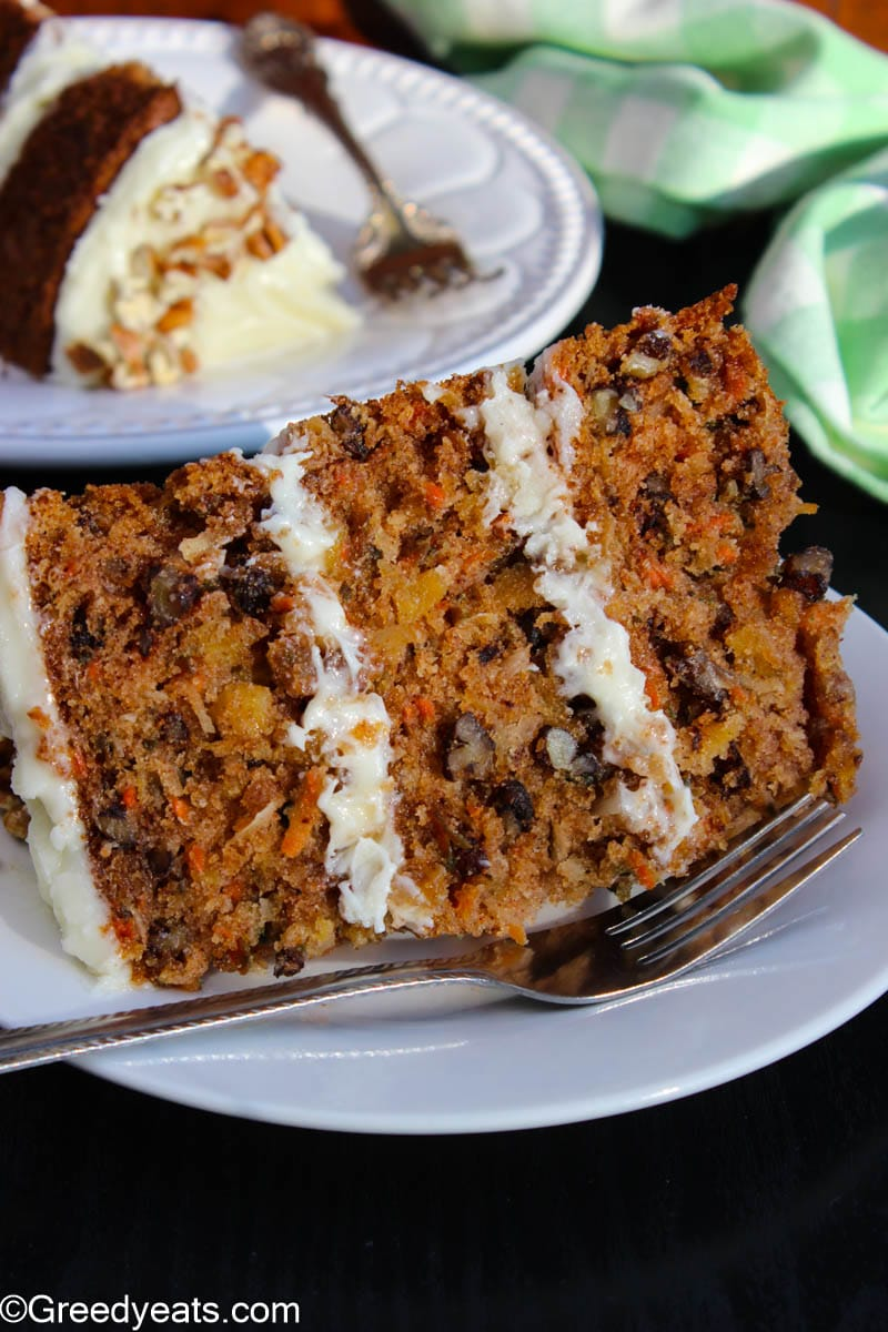 A slice of three layered Carrot cake with Pineapple, pecans and coconut shreds.