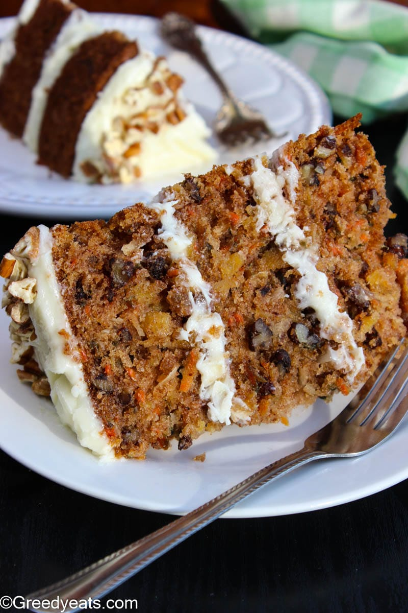 A slice of Moist Carrot Cake frosted with cream cheese frosting and topped with pecan chunks.