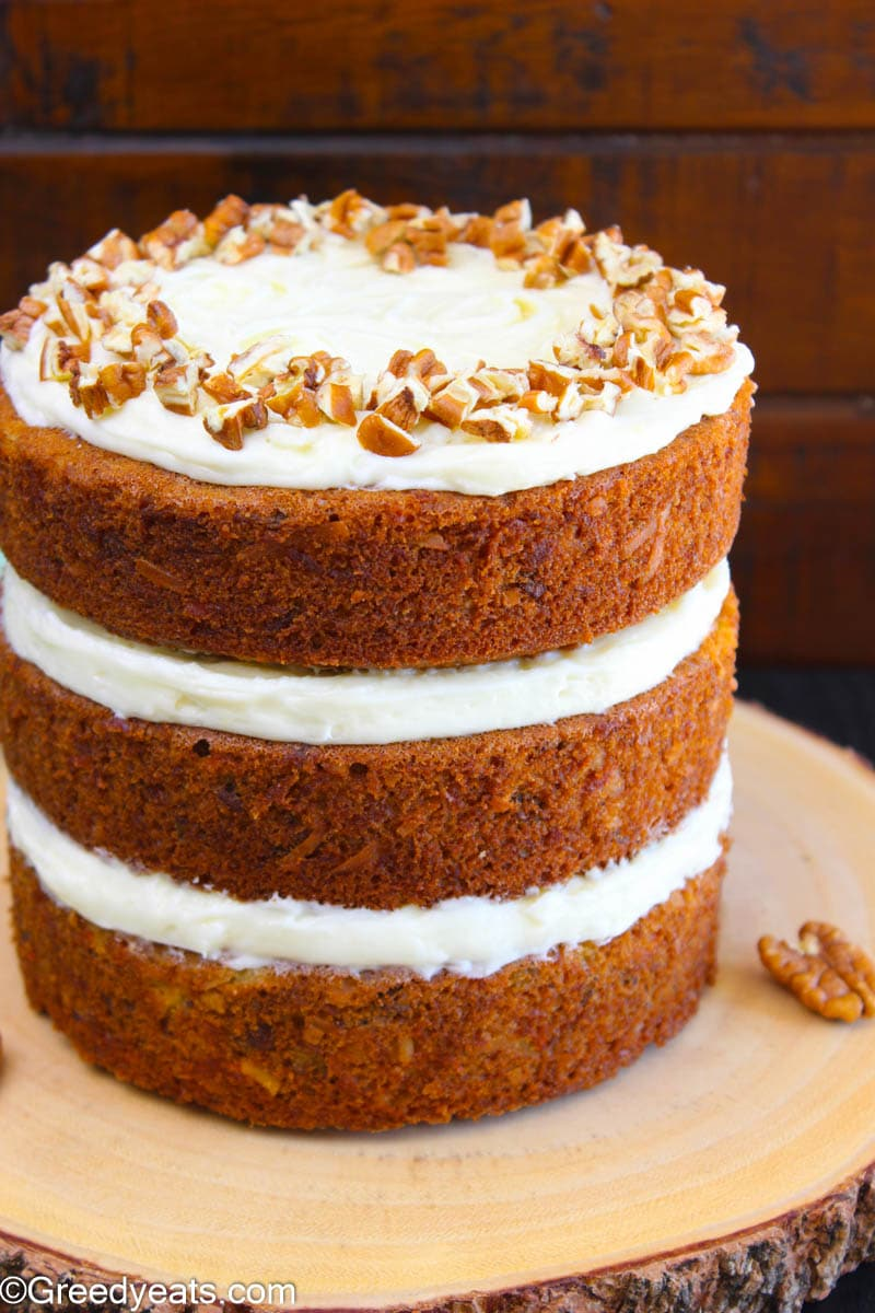 Three tiered naked Carrot Cake frosted with Creamy Cream Cheese Frosting.