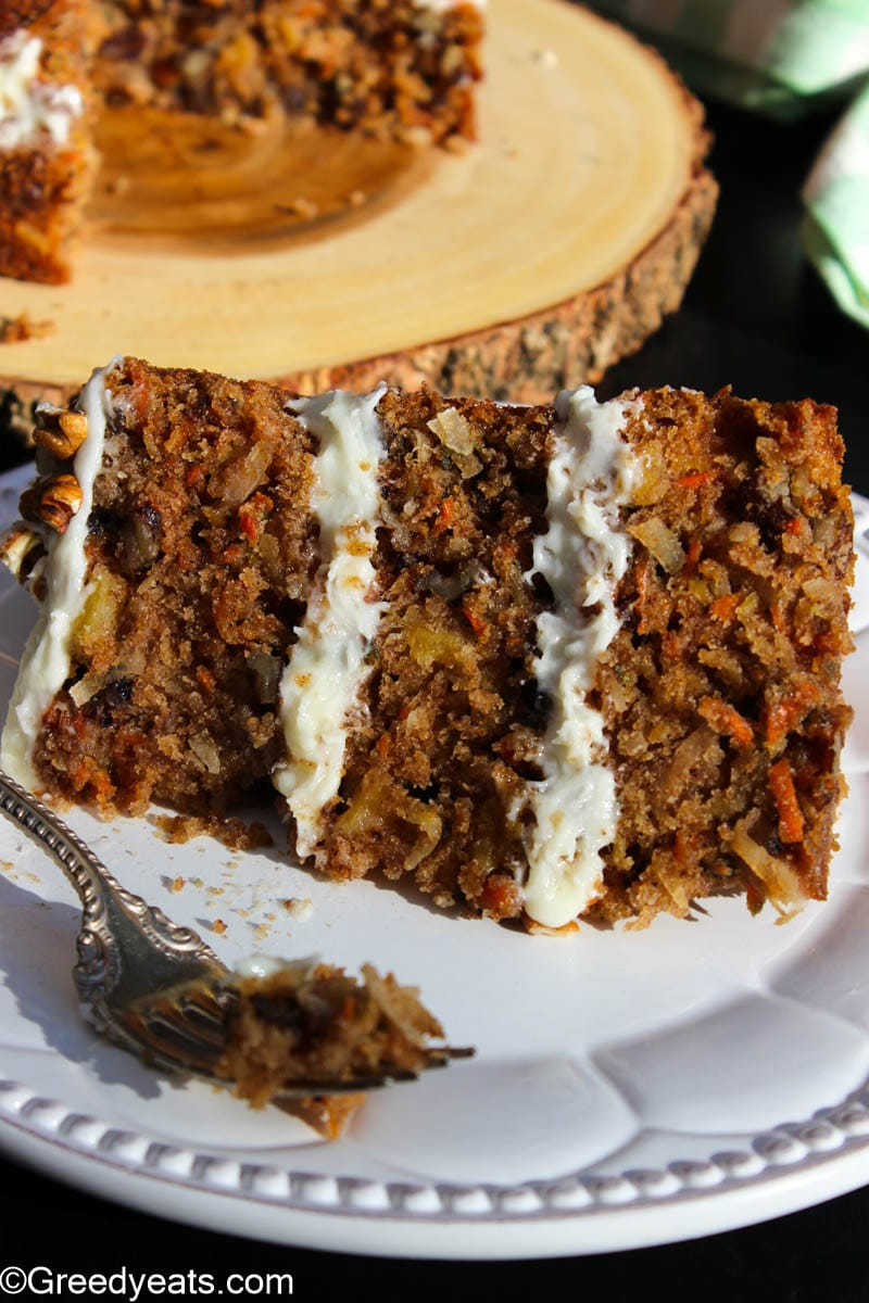 Soft and moist slice of three layered Carrot Cake with cream cheese frosting.