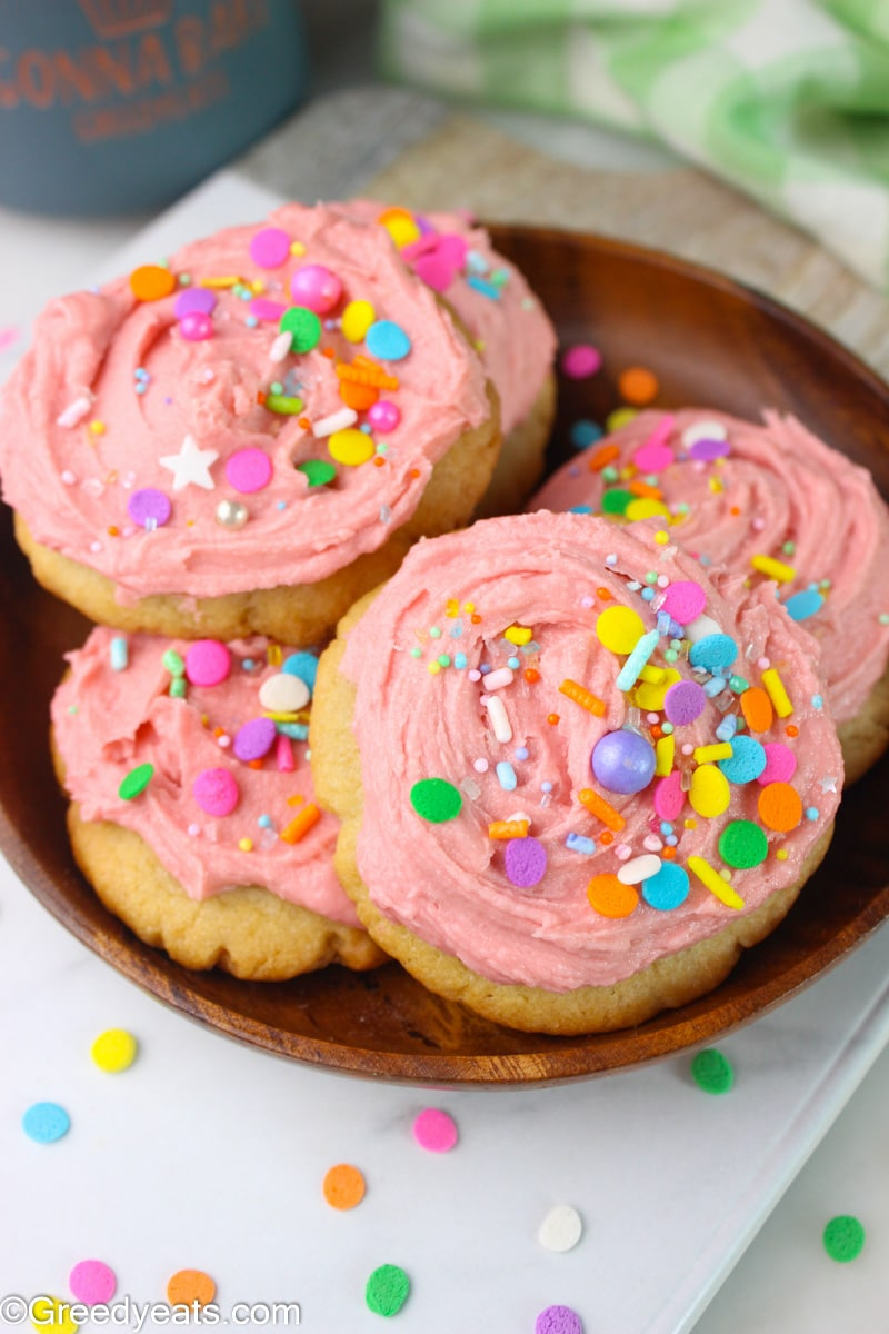 Swig Cookies baked as no roll sugar cookies frosted with pink frosting, topped with pastel sprinkles.