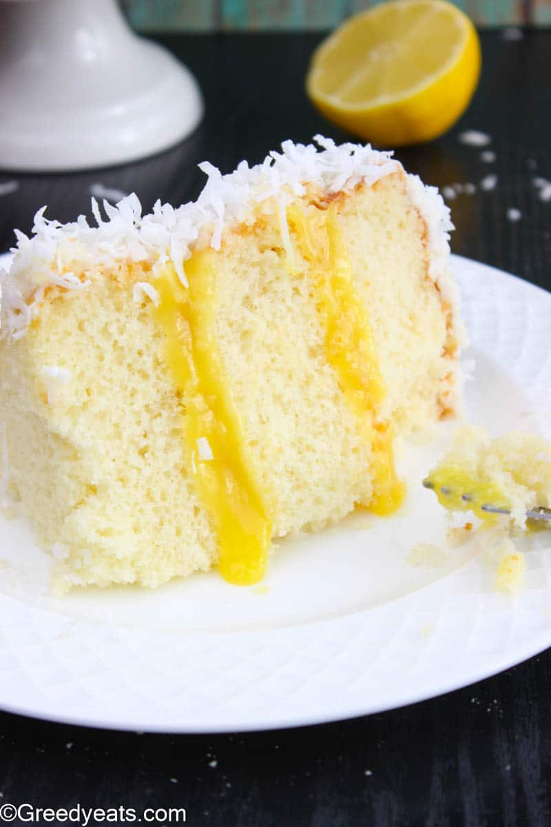 Soft and moist Coconut Cake with Lemon Filling on a white plate.