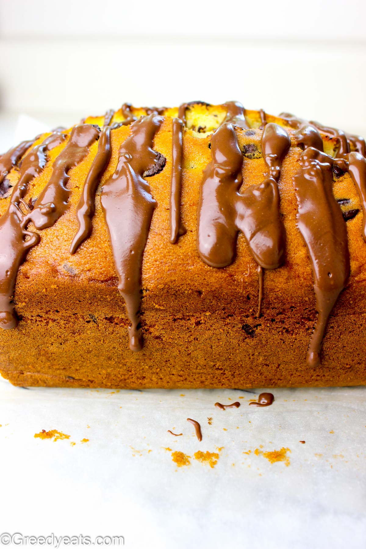 Soft and buttery Pound Cake drizzled with chocolate ganache kept on a parchment paper.