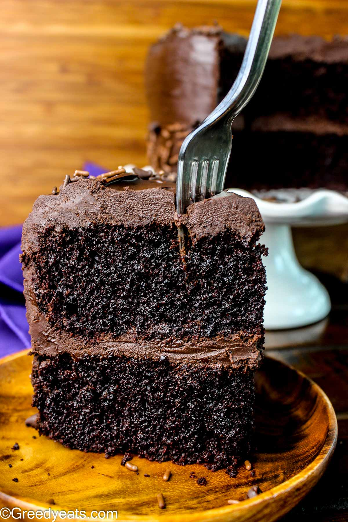 A Slice of one bowl chocolate cake topped with chocolate ganache kept on a wooden plate.