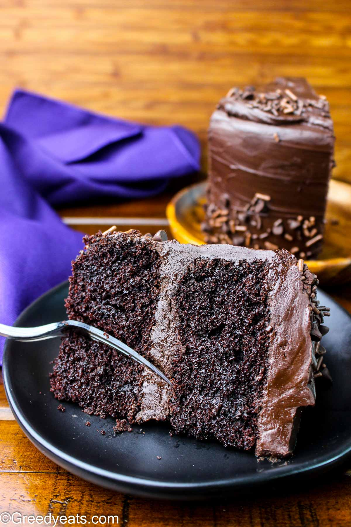 Tender and moist chocolate cake slice topped with chocolate ganache.