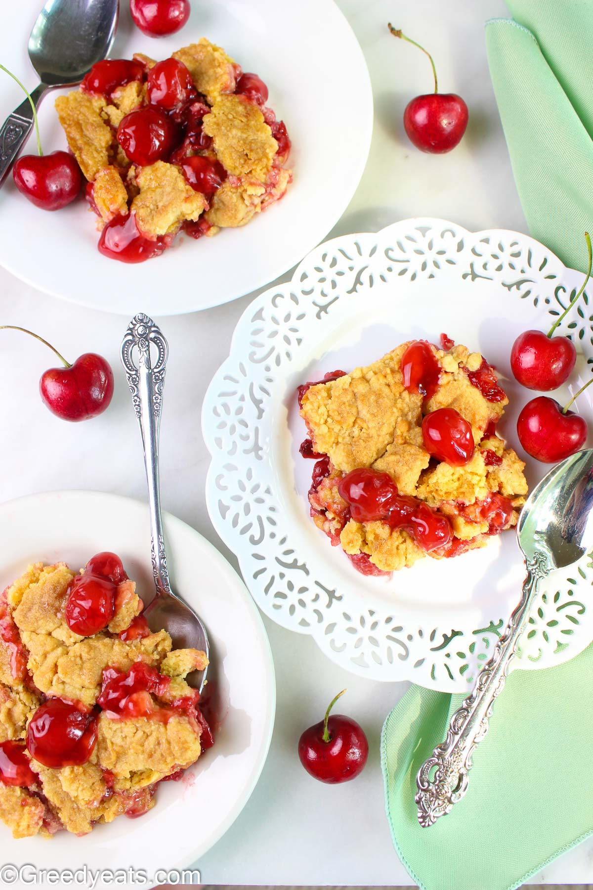 Cherry dump cake slices with fresh cherries served in white plates.