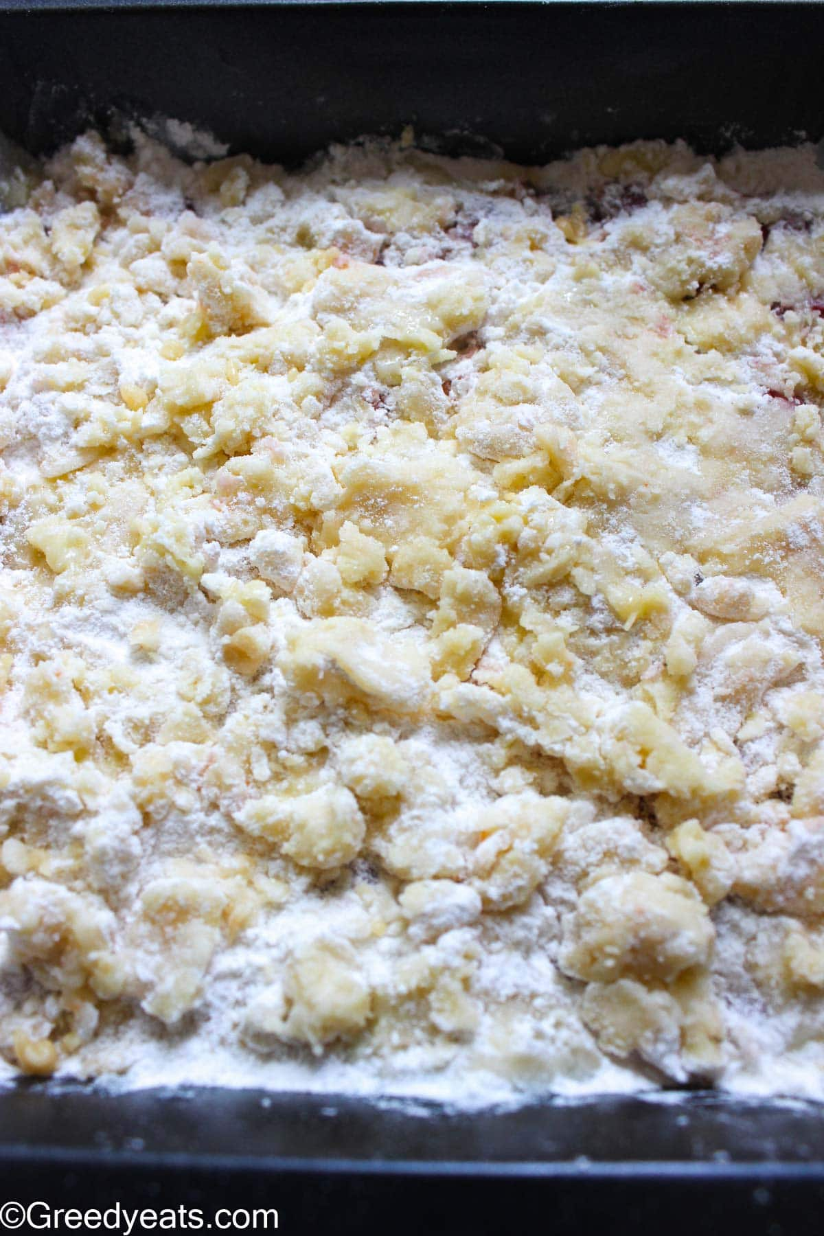 Unbaked cake crumbs, mixed with melted butter in a baking pan.
