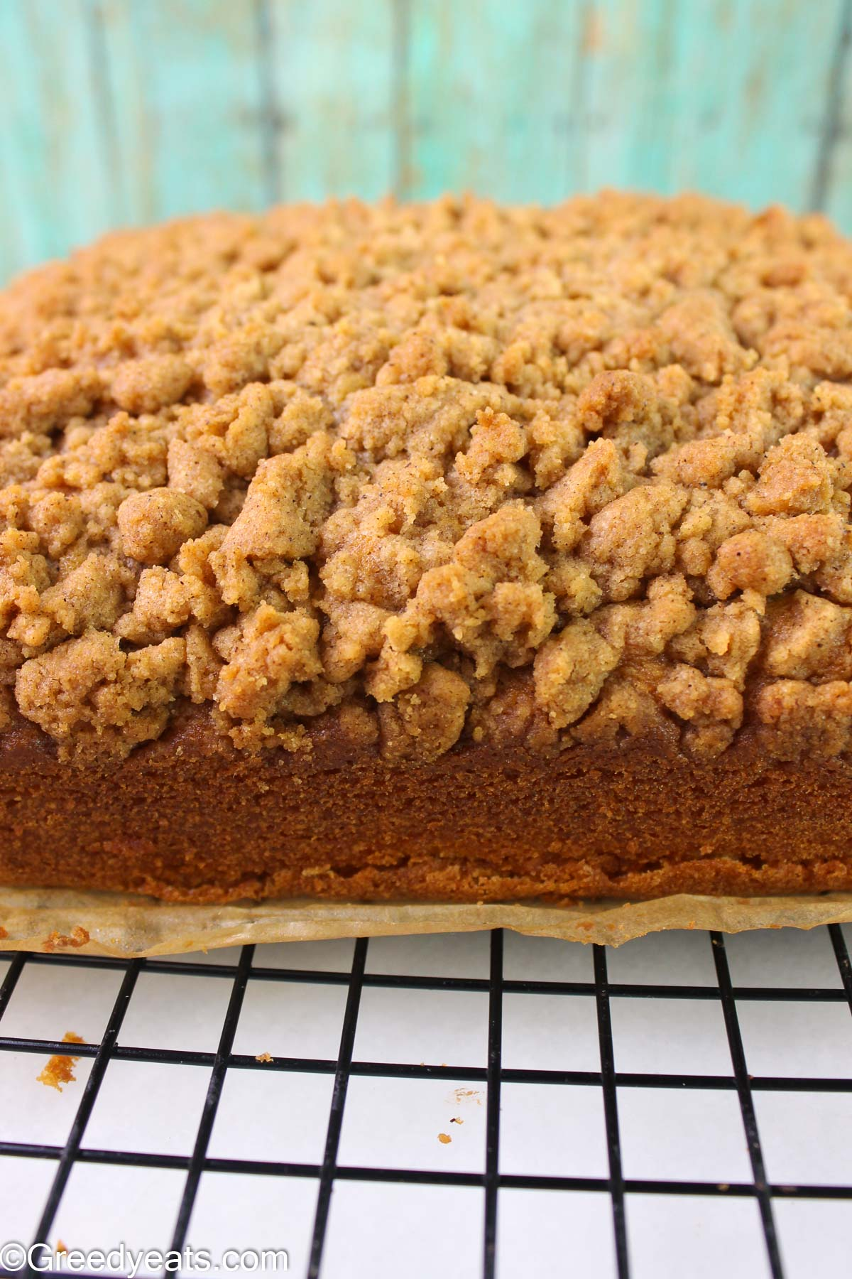 Homemade coffee cake with thick cinnamon crumb topping cooling on a wire rack.