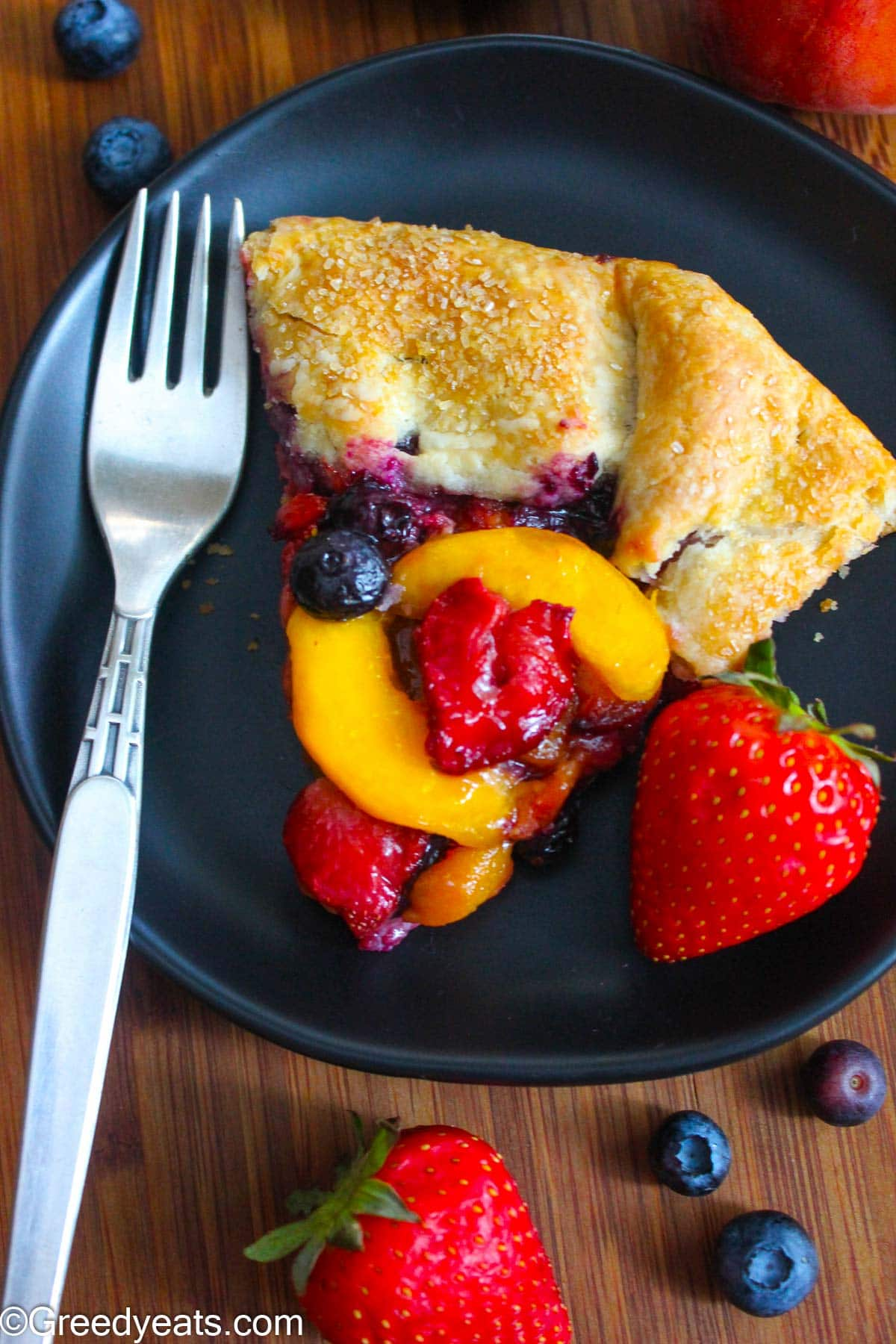 A slice of flaky Galette on black plate with peach and berries filling.