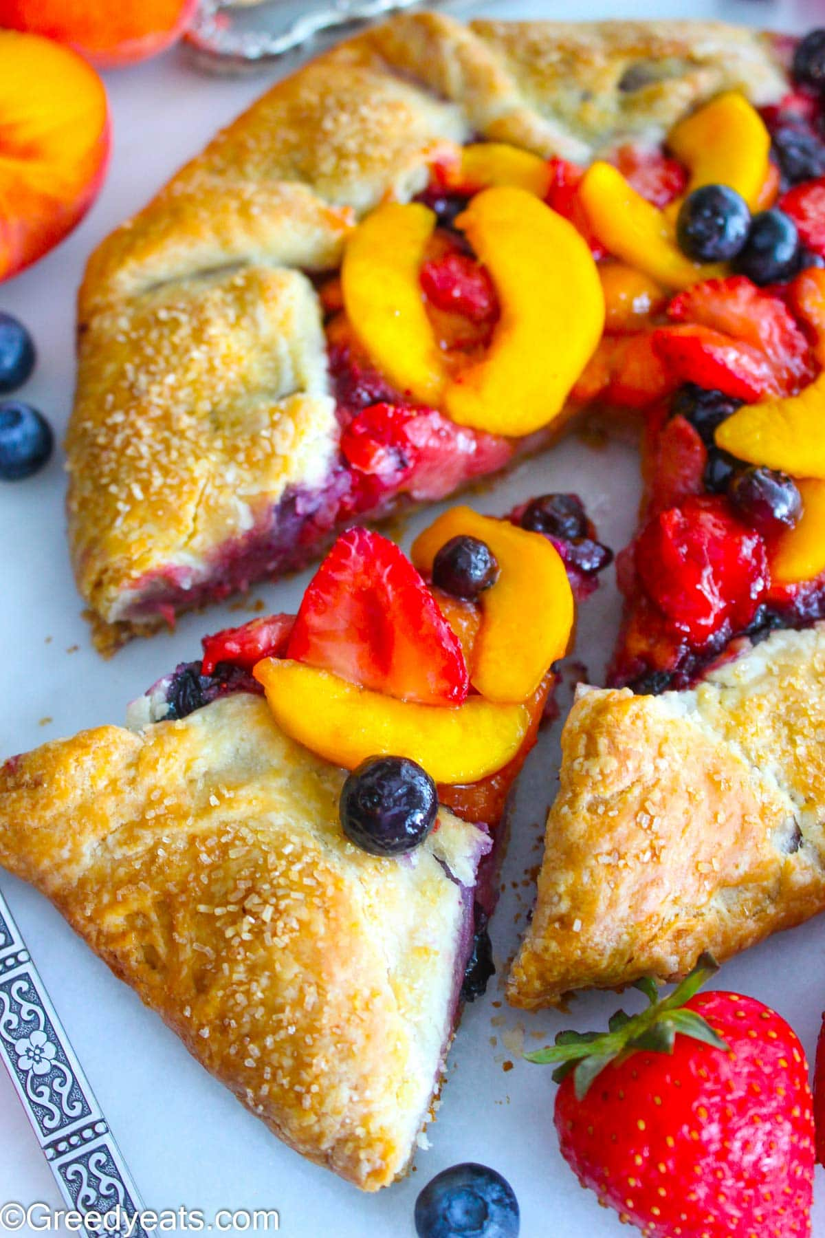 Buttery and flaky Peach Galette topped with coarse sugar and filled with berries filling.