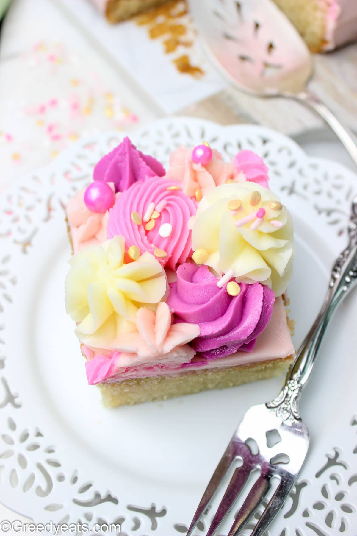 A slice of moist and easy Vanilla cake frosted with piped vanilla buttercream frosting.