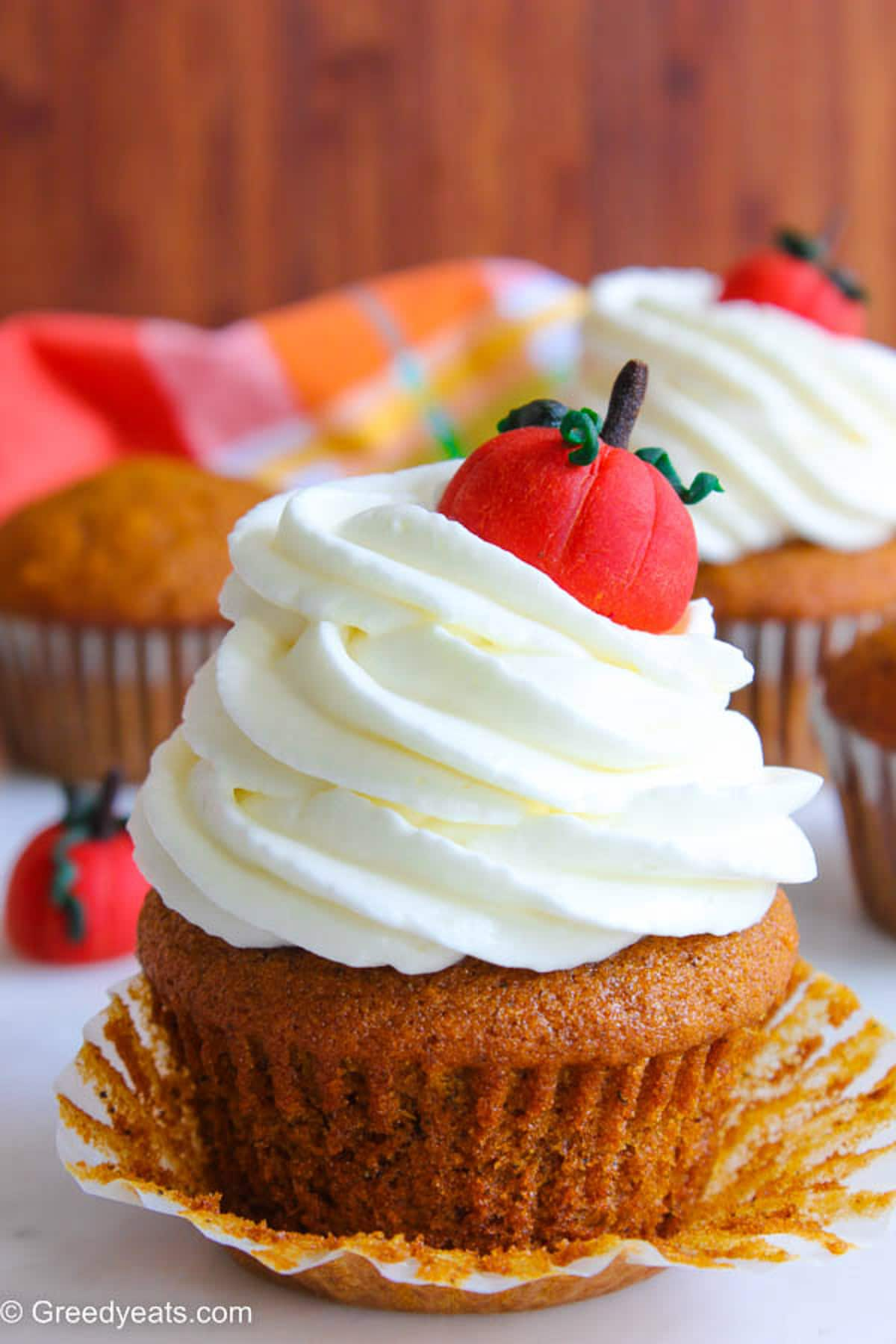 Fluffy and moist Pumpkin Cupcake topped with cream cheese frosting swirls and pumpkin topper.