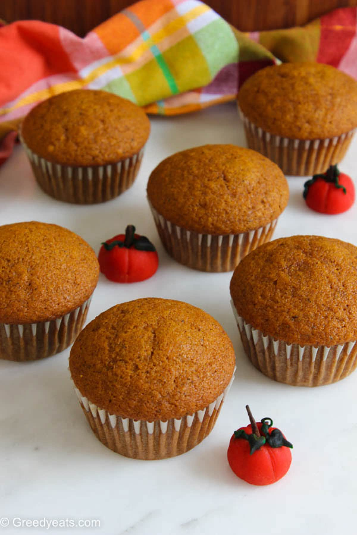 Freshly baked Pumpkin Cupcakes in white cupcake liners, cooling down before frosting.