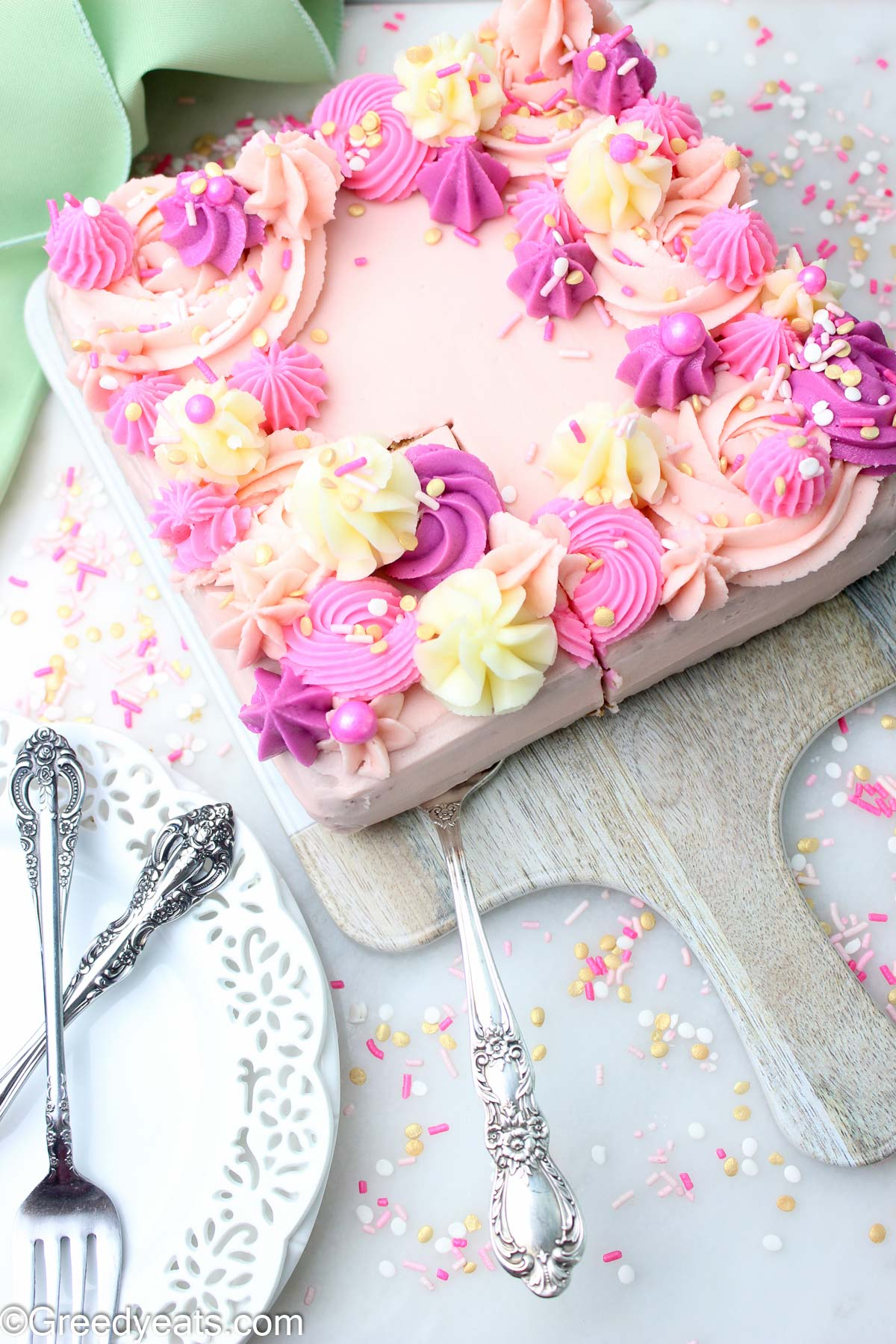 Best Vanilla Cake baked in a square pan with vanilla frosting tinted with dusty pink and pink gel food colorings.