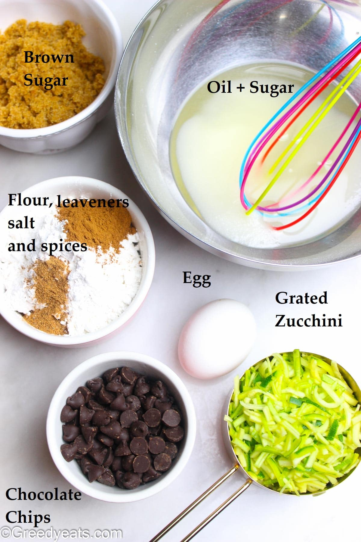 Ingredients like oil, brown sugar, granulated sugar, egg, grated zucchini and spices to make bread.
