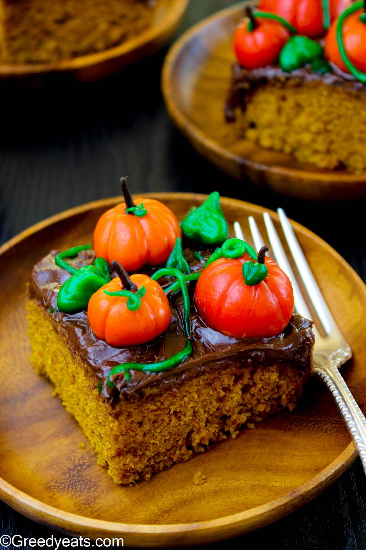 A slice of soft and moist Pumpkin Cake topped with whipped chocolate frosting.