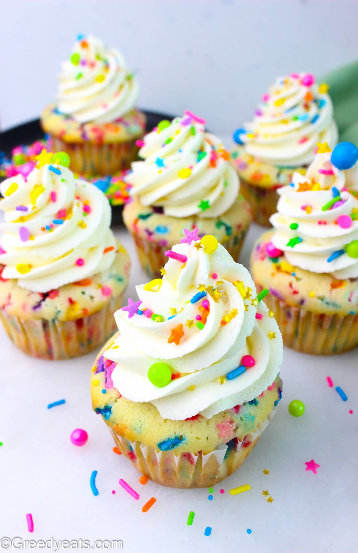Homemade Funfetti Cupcakes topped with Vanilla Buttercream Frosting kept on a white board.