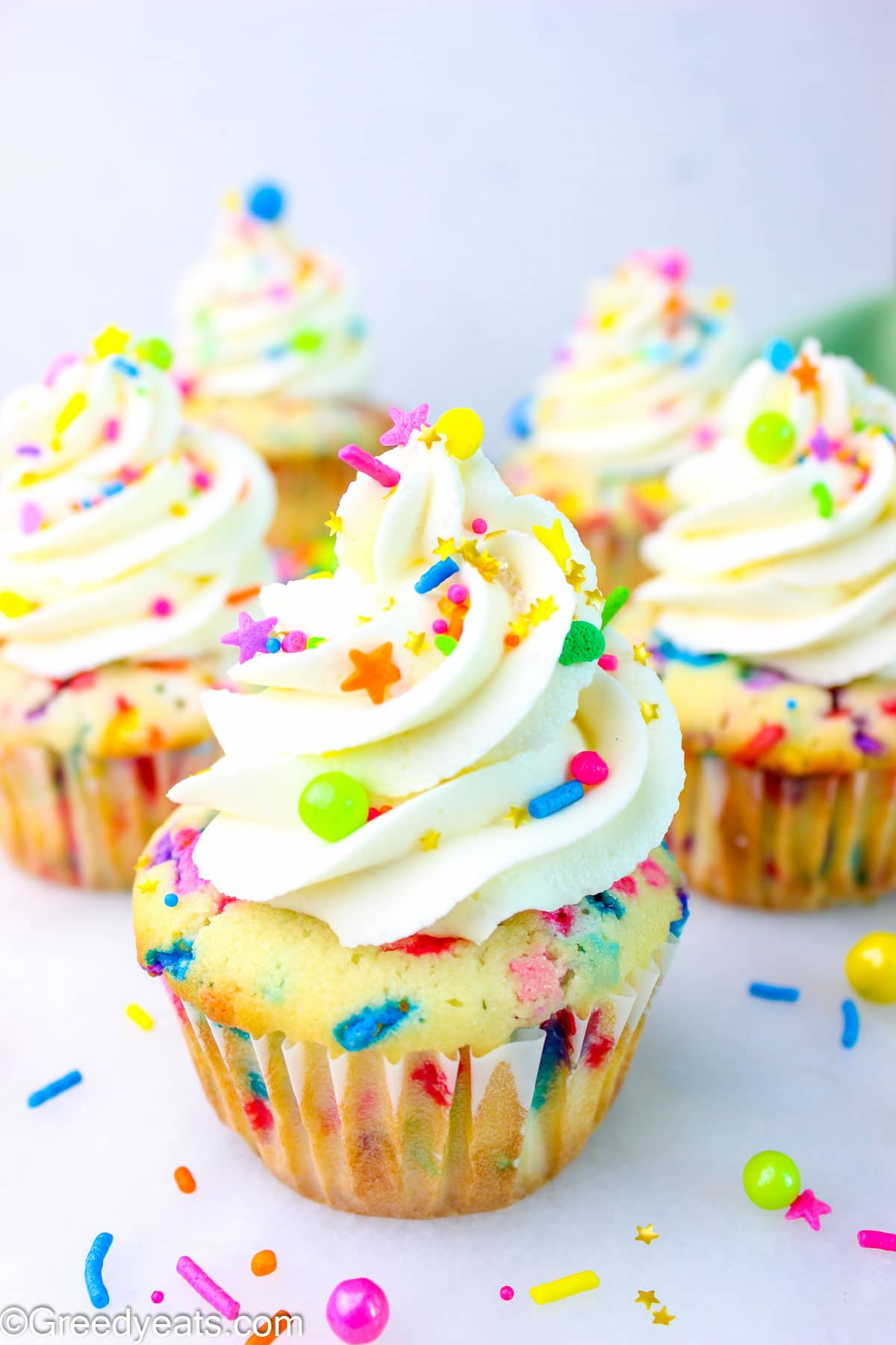 Fluffy Funfetti Cupcakes topped with swirls of Vanilla Buttercream Frosting and rainbow sprinkles.