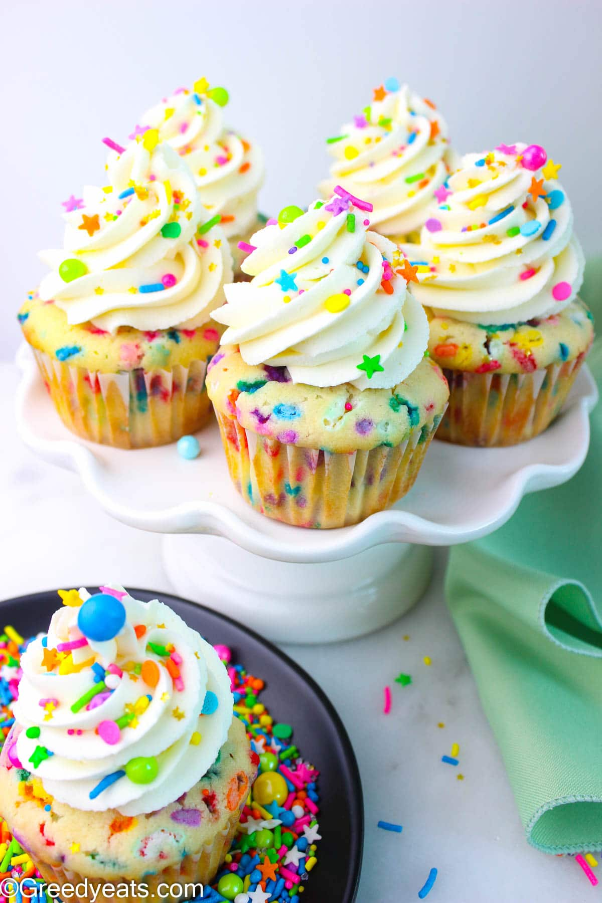 Funfetti Cupcakes Recipe made with sour cream, topped with Vanilla Buttercream kept on cake stand.