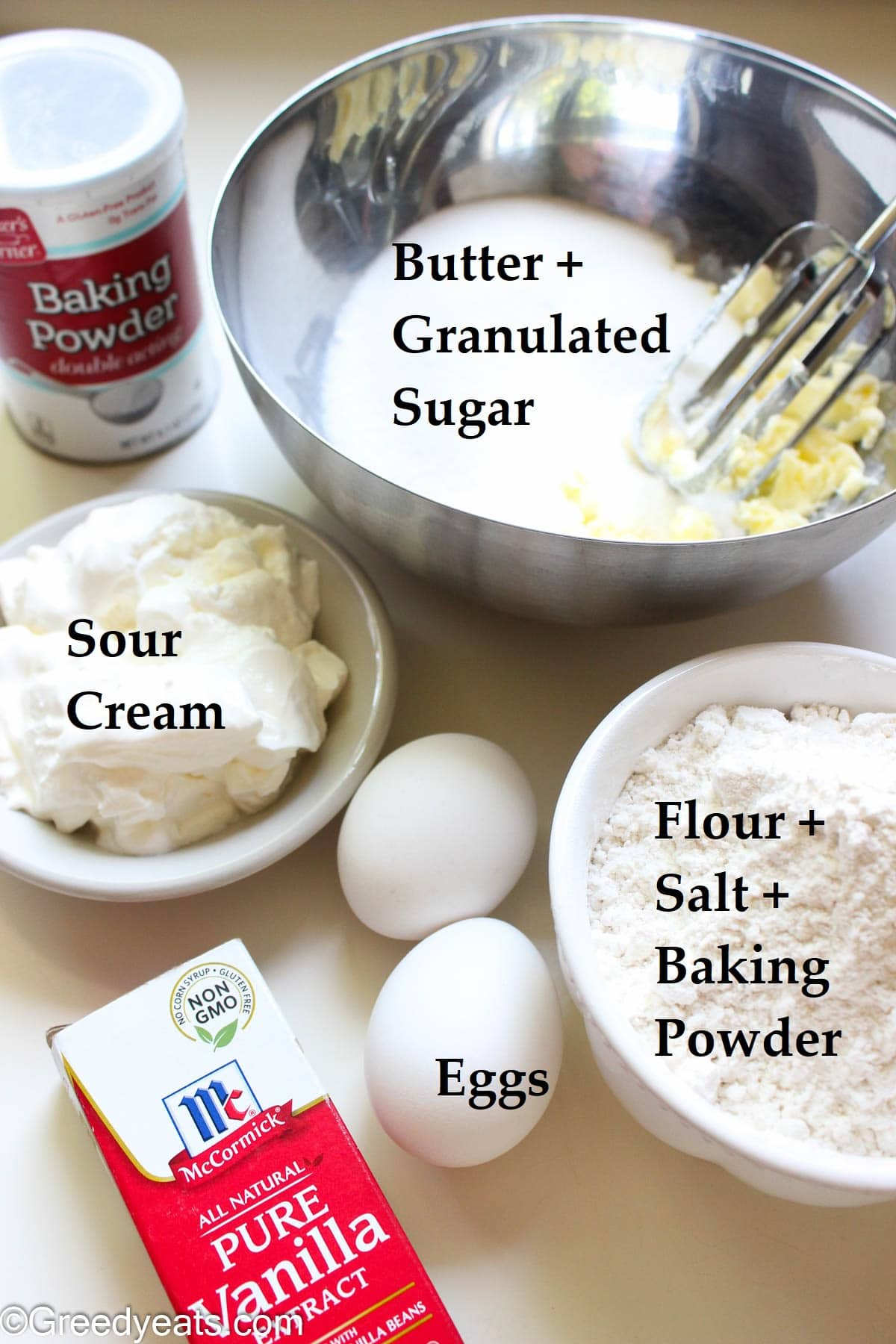 Ingredients like butter, sugar, flour, eggs and sour cream to make confetti cupcakes.