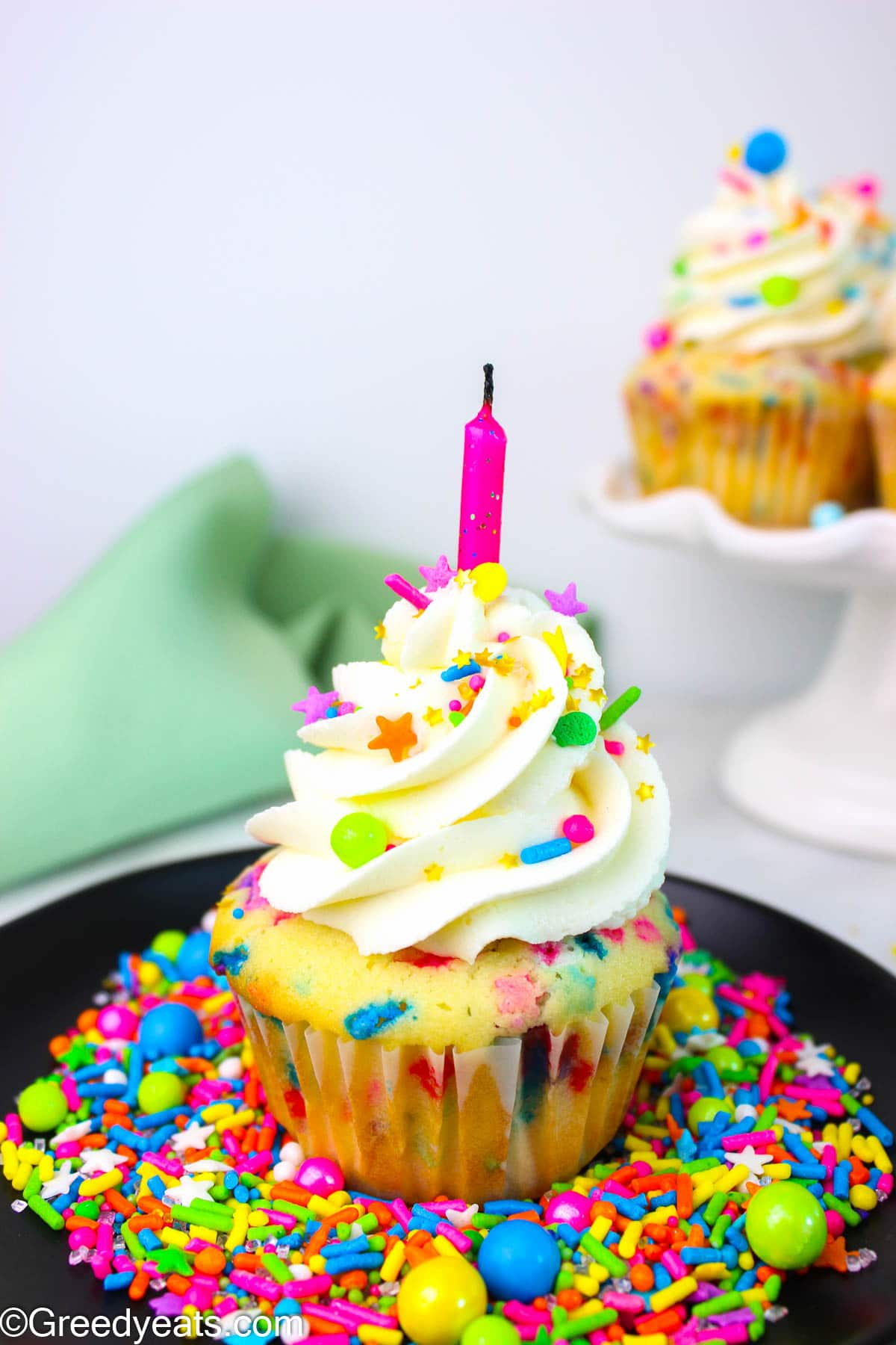 Funfetti Cupcake topped with Vanilla Buttercream and rainbow sprinkles on a black plate.