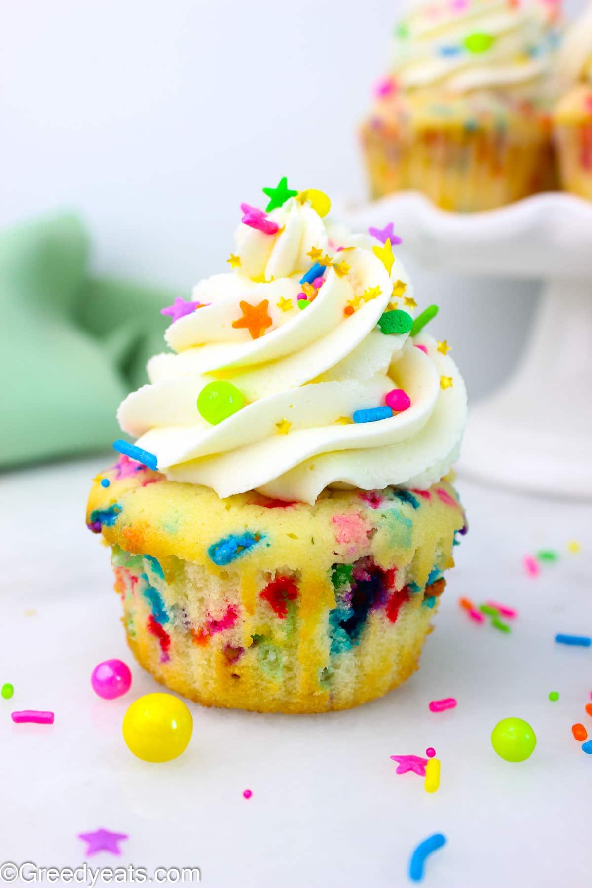 Confetti Cupcake with Creamy Vanilla Buttercream kept on a white board.