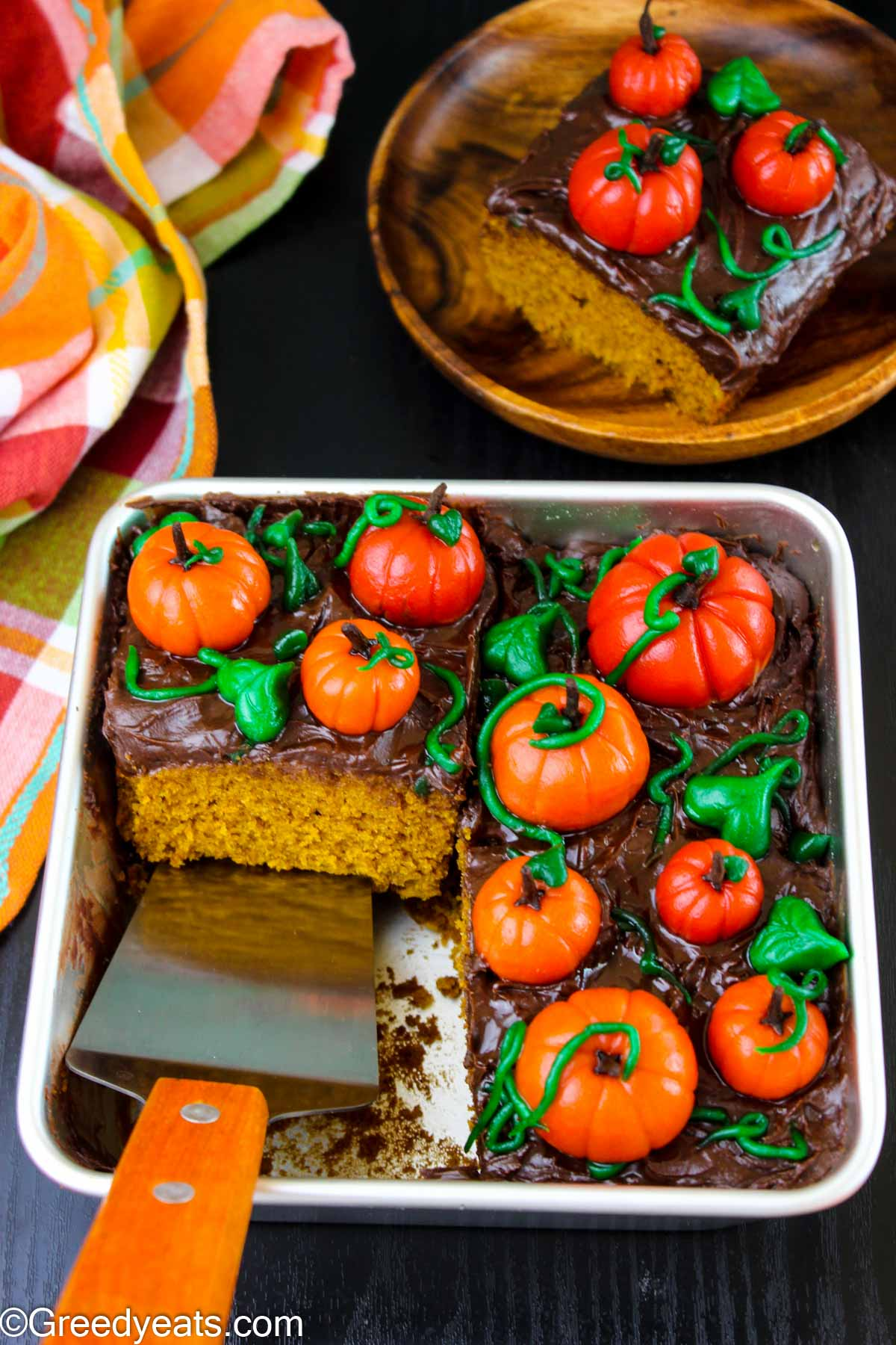 Soft and moist Pumpkin Cake frosted with whipped ganache and fondant pumpkins.