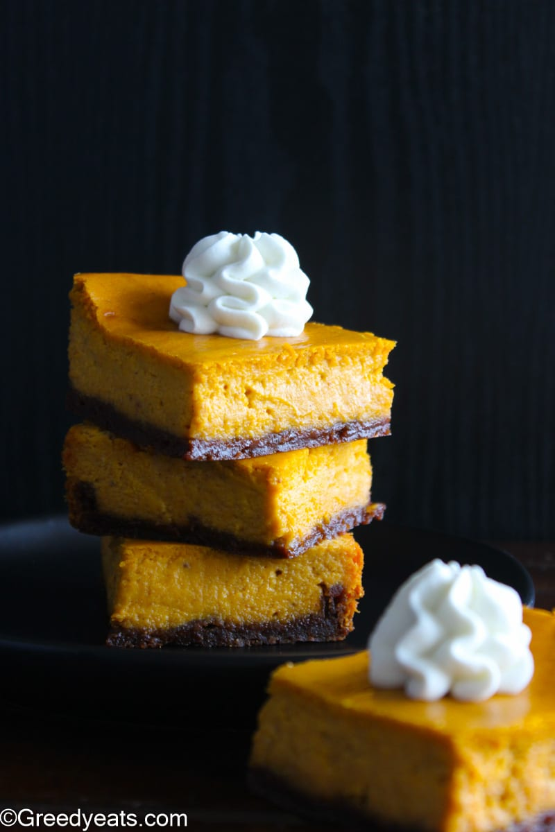 A stack of creamy and thick Pumpkin Pie Bars topped with a swirl of whipped cream.