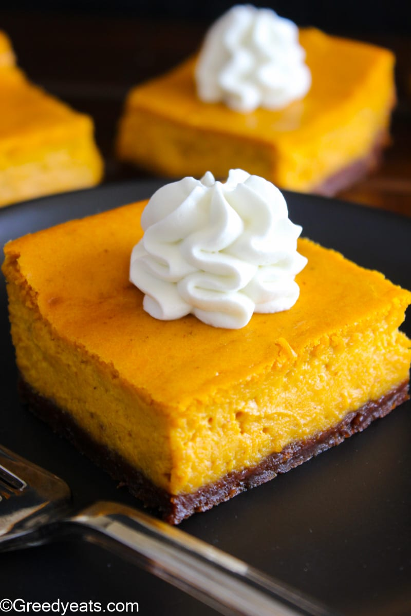 Creamy and rich Pumpkin Cheesecake Bars with graham cracker crust topped with whipped cream.