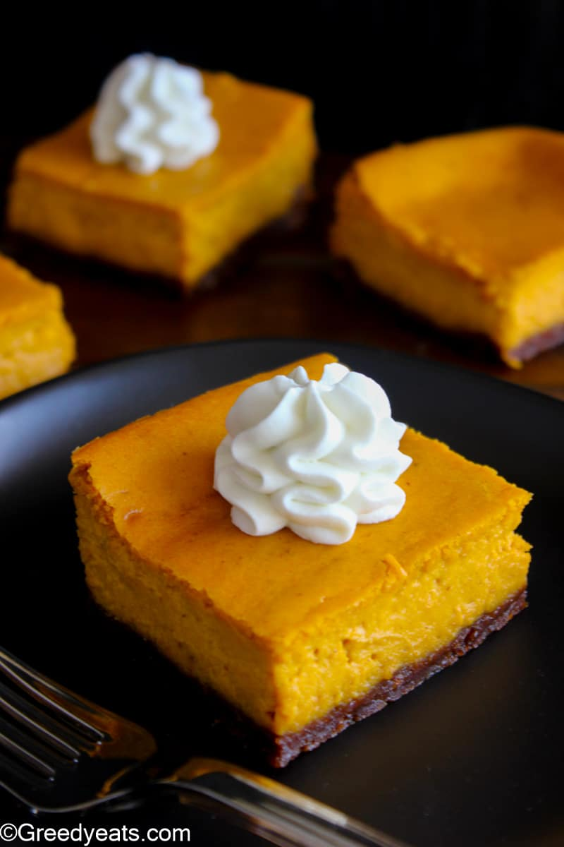 Pumpkin Pie Bars with buttery crust underneath and whipped cream dollop on top.