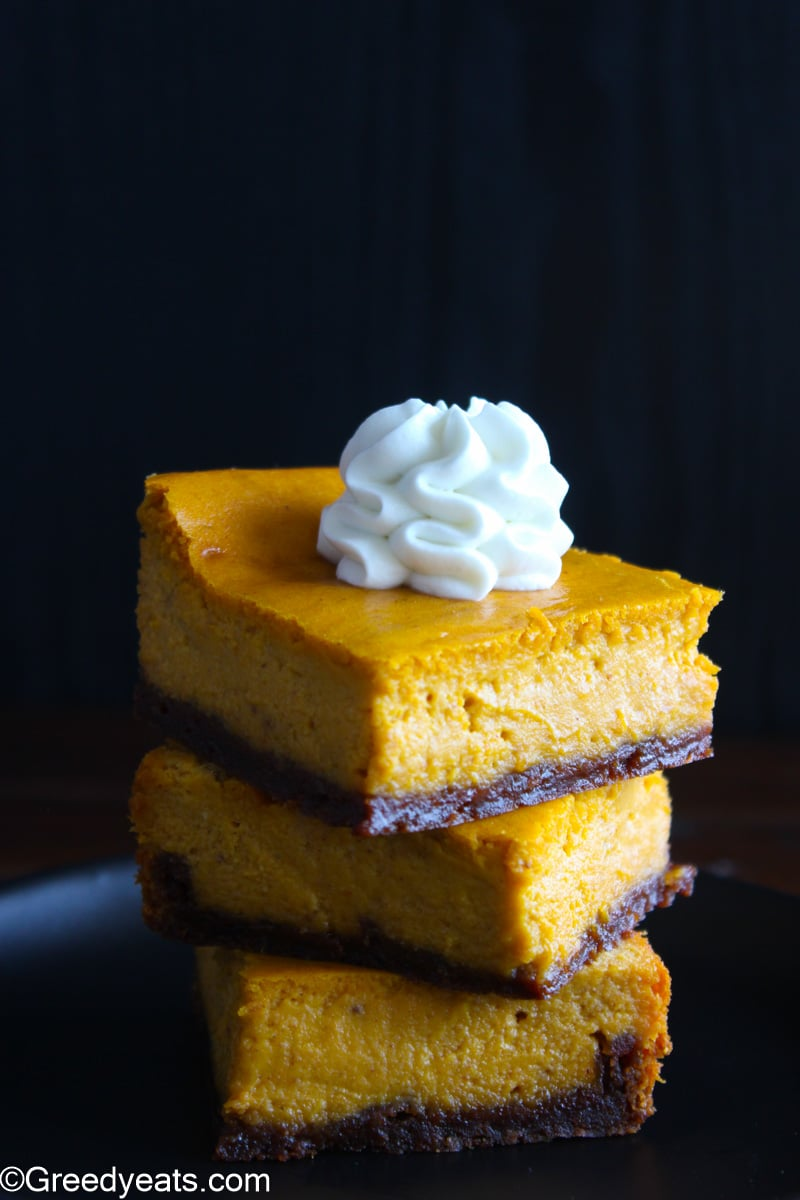 Pumpkin Pie bars recipe slices stacked and topped with whipped cream swirl.