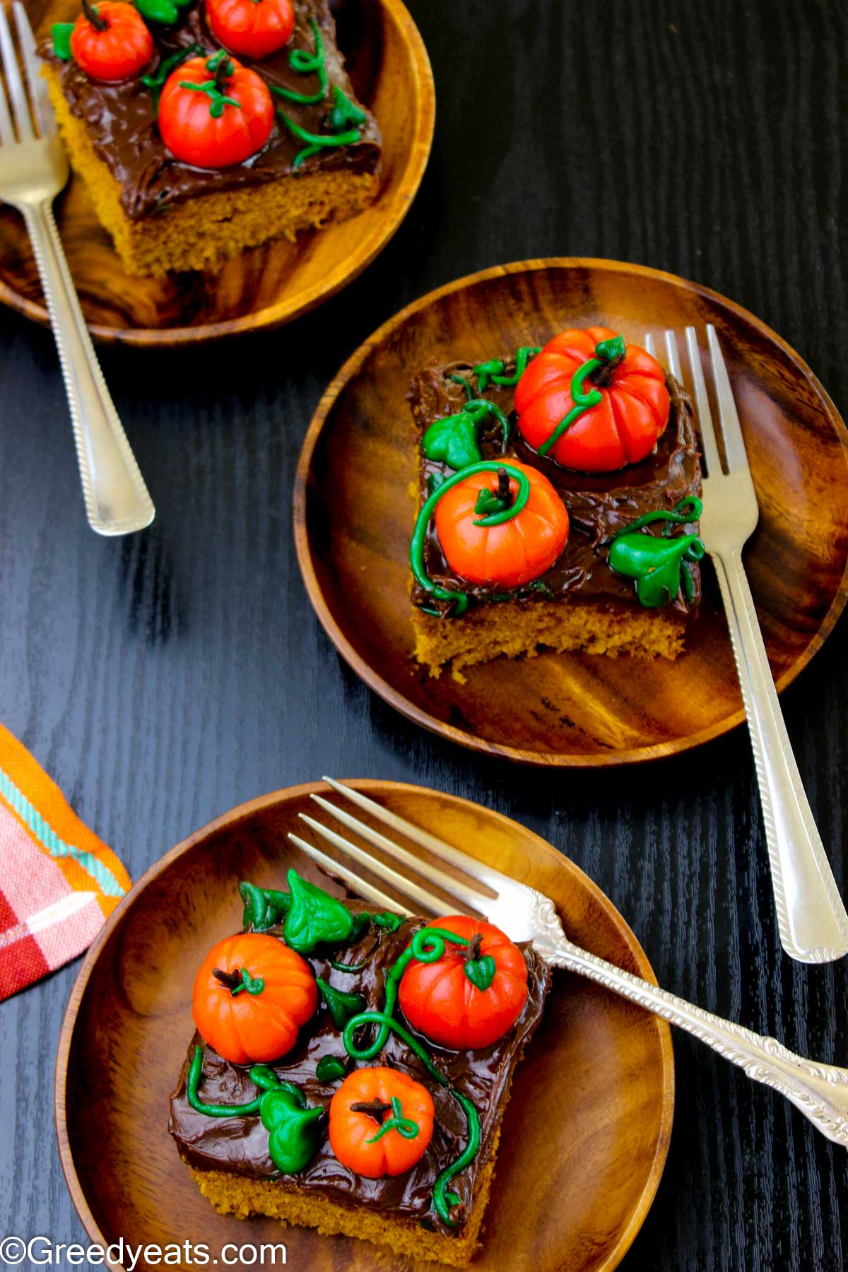 Slices of soft, moist and easy Pumpkin Cake recipe topped with whipped chocolate ganache and pumpkins.
