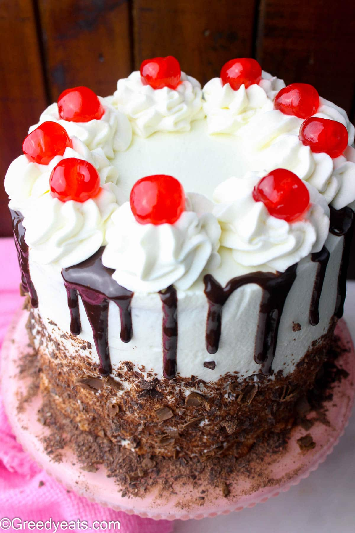Black forest cake topped with whipped cream topping and layered with cherries.